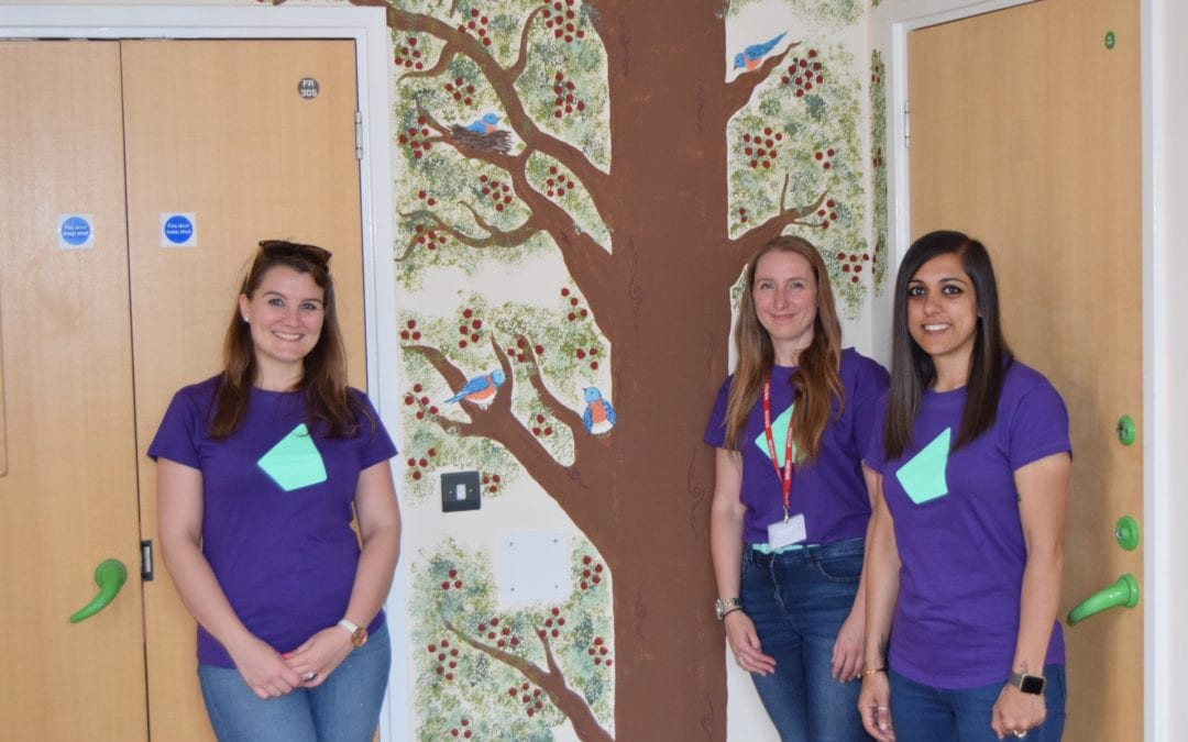 Photo of three IRESS staff members in front of the tree mural in the Willow Ward end of life room.